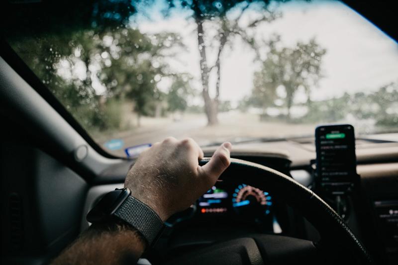 Blick aus einem fahrenden Auto mit Smartphone im Vordergrund