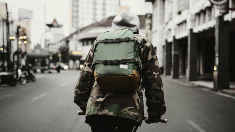 Ein Reisender auf seiner Fahrradtour durchstreift eine Stadt mit seinem Rucksack