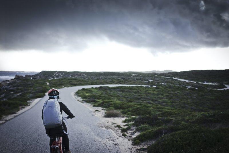 Eine Frau auf dem Fahrrad fährt durch eine kalte Gegend