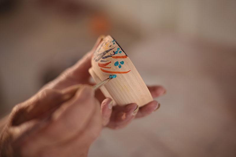 Eine Keramikschale wird bunt bemalt.