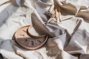 Getöpferte Tonschale in Mondform neben Töpferwerkzeugen