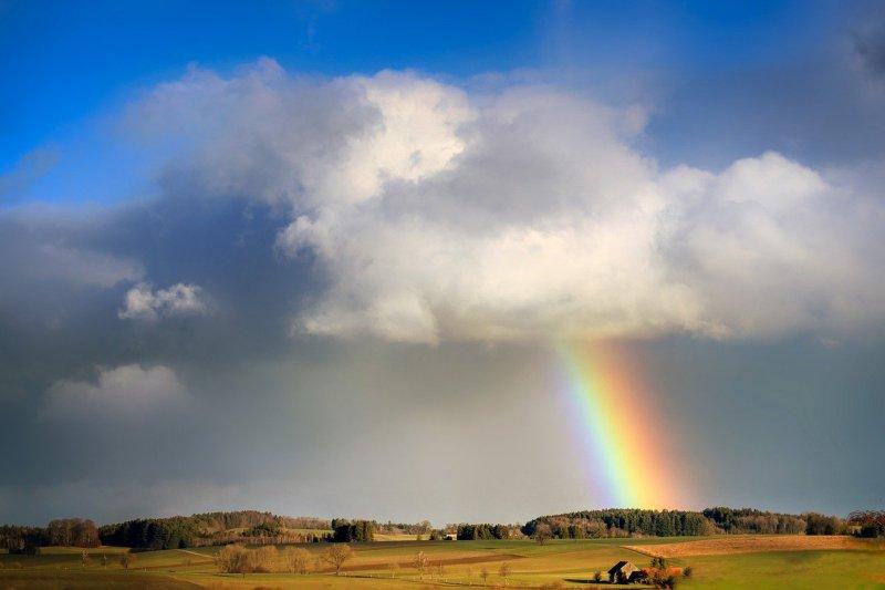 Landschaft mit Wolken, Regen und einem Regenbogen