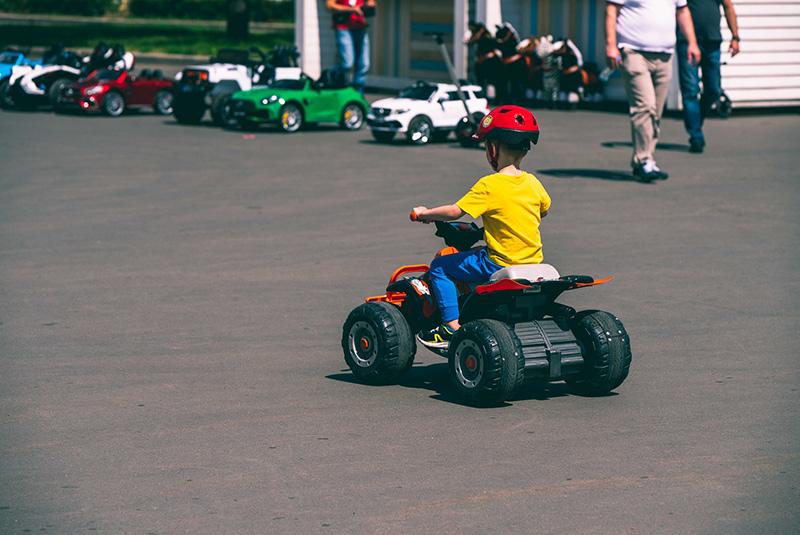 Kleiner Junge, Fahrer eines elektrischen Quads für Kinder mit gelben T-Shirt fährt auf Asphalt.