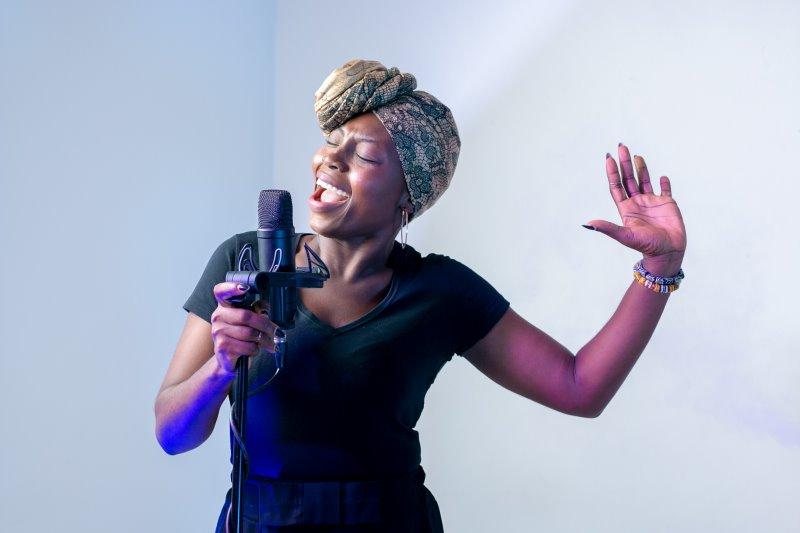 Eine Frau hält ein Mikrofon und singt.
