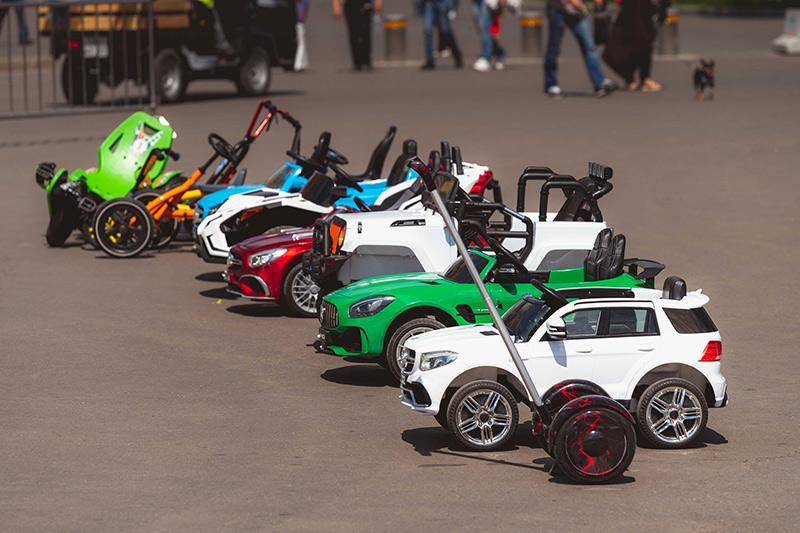 Verschiedene Typen von E-Autos für Kinder nebeneinander in einer Reihe aufgereiht.