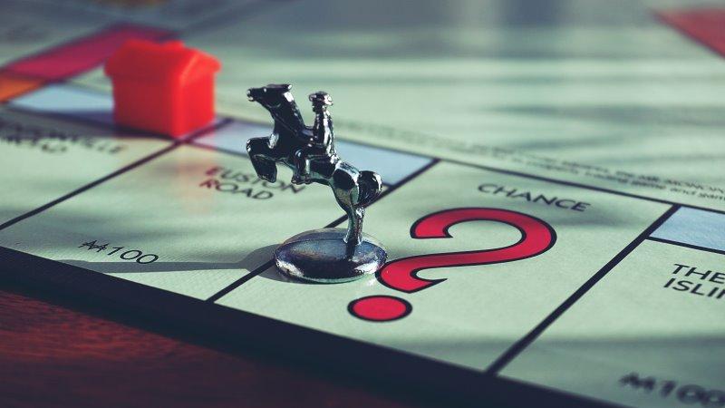 Eine Spielfigur befindet sich auf einem Monopoly Spielbrett
