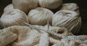 Zwei Strumpfstricknadeln und beige Wolle