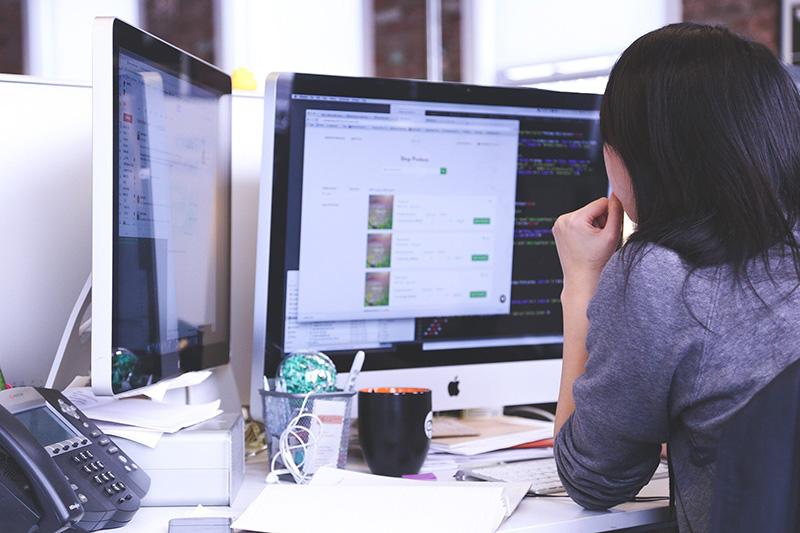 Frau an ihrem Arbeitsplatz mit 2 Monitoren