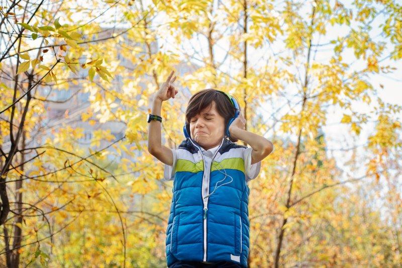 Kind mit Köpfhörer in der Natur hört Musik