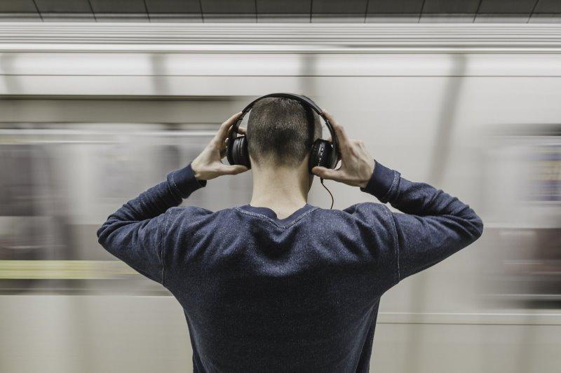 Ein Mann setzt sich Kopfhörer auf, während eine U-Bahn vorbei fährt.