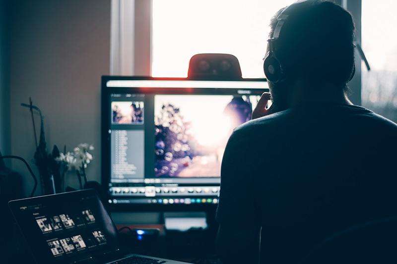 Mann sitzt vor einem Laptop und einem Monitor