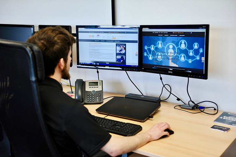 Ein Mann sitzt vor zwei Bildschirme