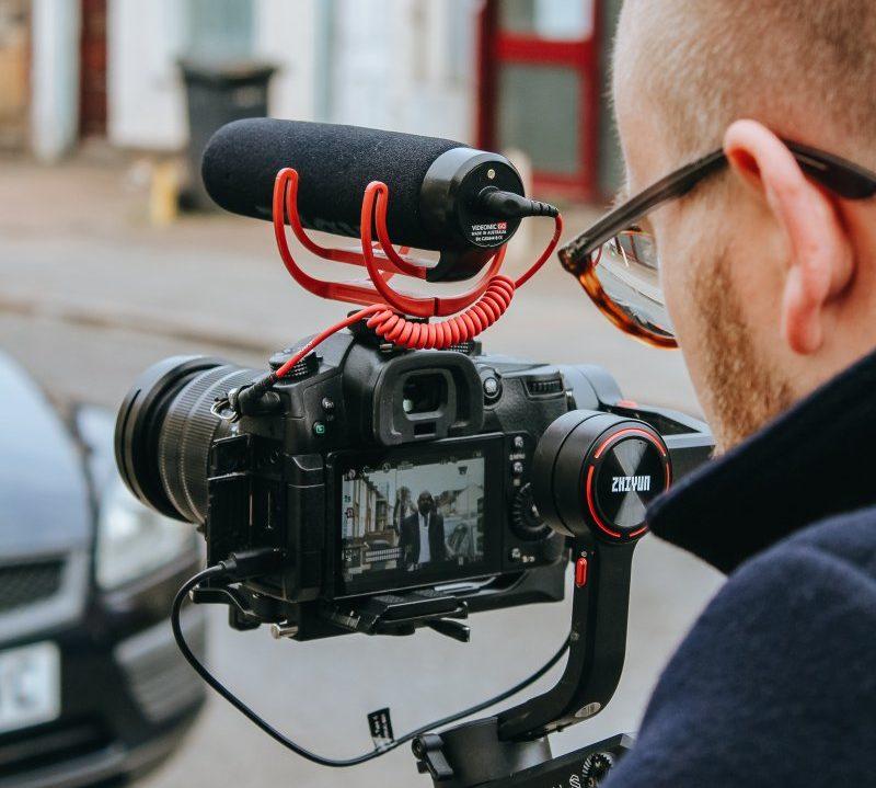 Mann dreht Video mit Kameramikrofon