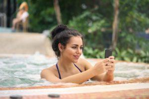 Outdoor Whirlpool, Frau anSmartphone
