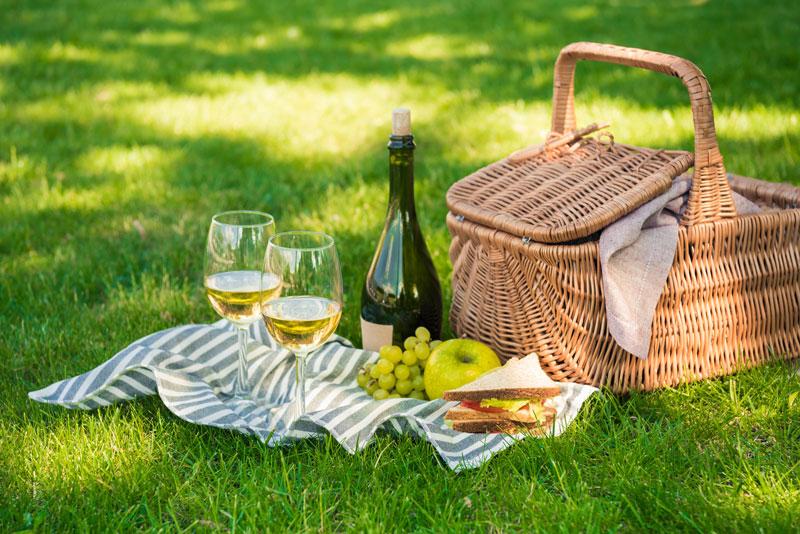 Picknickkorb auf einer Wiese, sowie gefüllte Weingläser, eine Weinflasche und Speisen auf einer Decke ausgebreitet