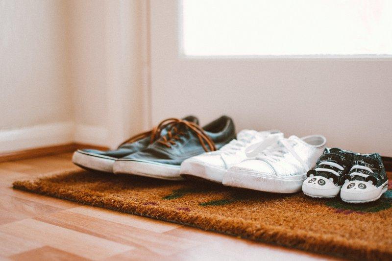 Schuhe auf einer Schuhmatte vor einer Tür.