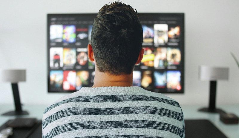 Mann schaut auf 75 Zoll Fernseher