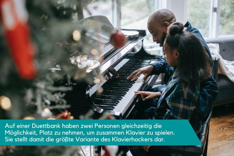 Klavierbank für zwei Personen, auf der ein Vater mit seinem Kind Klavier spielt