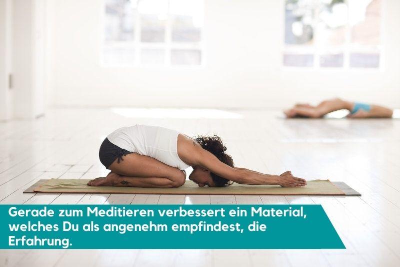 Frau meditiert auf ihrer Yogadecke