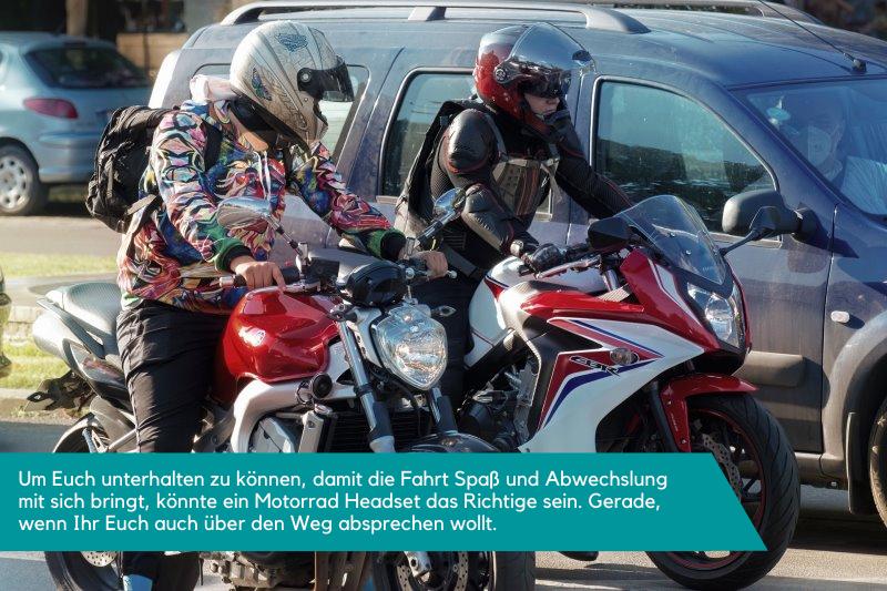 Zwei Motorradfahrer sitzen auf dem Motorrad und stehen. Sie sprechen sich ab.
