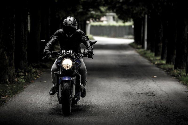 Motorradfahrer fährt auf einer langen geraden Straße