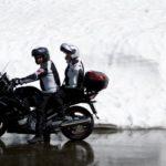 Motorradfahrer und Sozius unterhalten sich im Stand auf dem Motorrad
