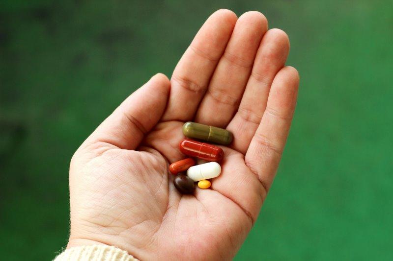Nahaufnahme Hand mit Multivitamin-Tabletten