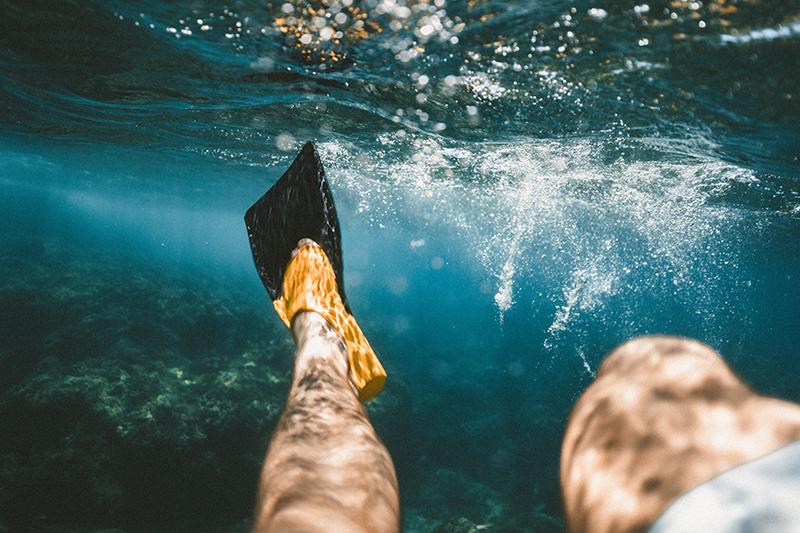 Mann mit Schnorchelflossen im Meer