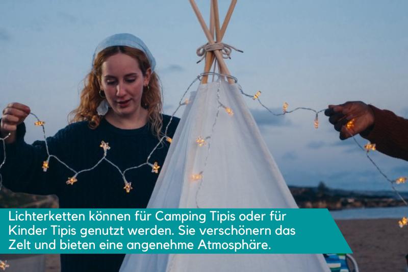 Eine Frau hängt eine Lichterkette auf ein Tipi Zelt