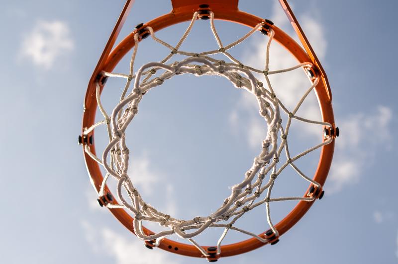 Ein Blick durch das Netz eines Basketballkorbs.