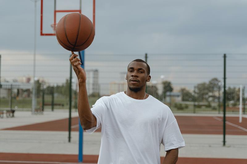 Ein Mann der einen Basketball auf seinem Finger dreht