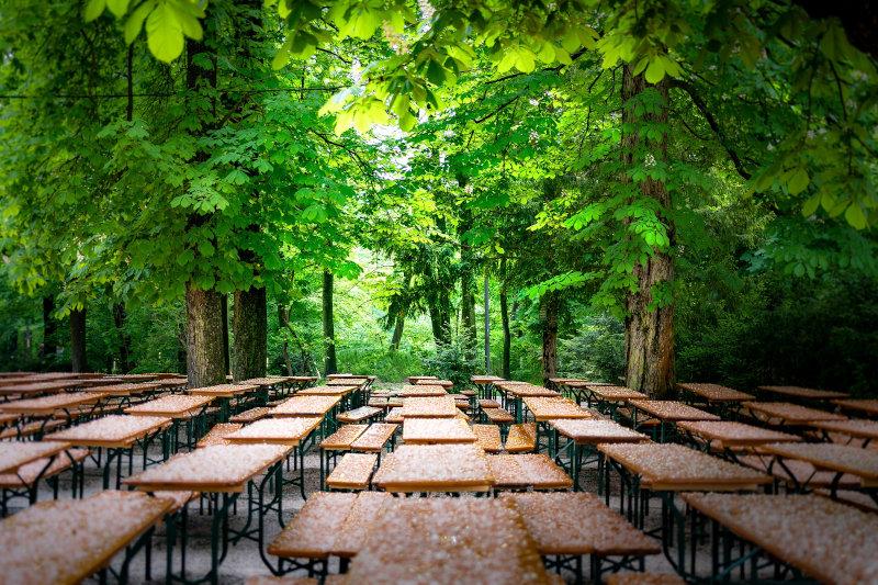 Bierbänke und Biertische in einem Park unter grünen Bäumen