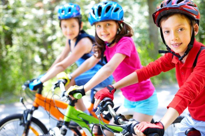 drei Kinder auf Kinderfahrrad sitzend mit Helm