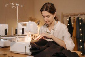 Frau sitzt an einer Coverlock Nähmaschine und näht Stoff