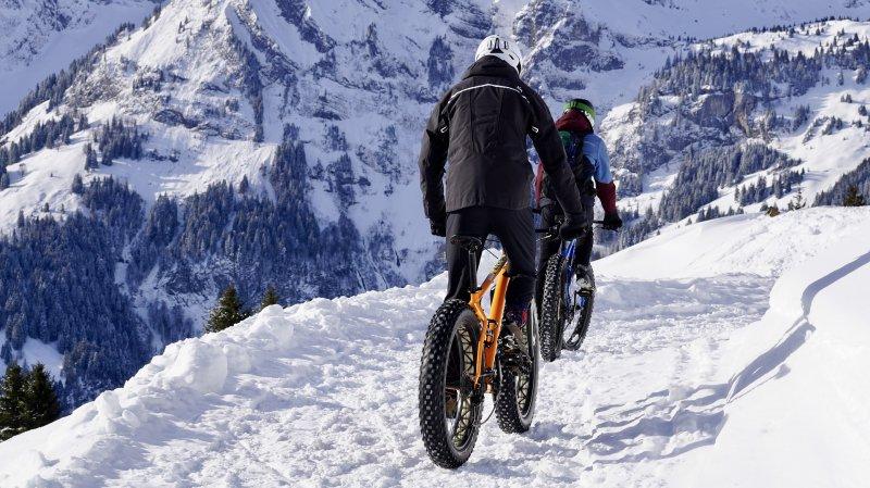 Fahrradfahrer, die im Schnee mit Hardshelljacken Fahrrad fahren