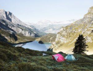Zwei Zelte stehen in einem Tal, umgeben von Bergen