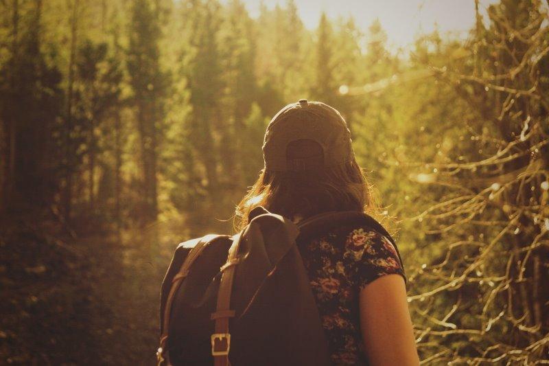 Eine Frau geht gerade mit einem großen Rucksack wandern im Wald