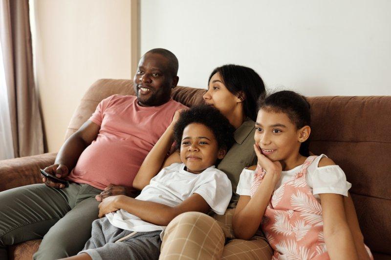 Familie, die mit Universalfernbedienung ihren Smart-TV steuert.