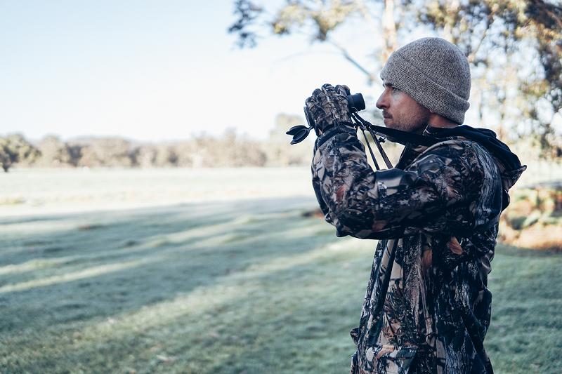 Ein Jäger mit Entfernungsmesser-Fernglas in seinen Händen.