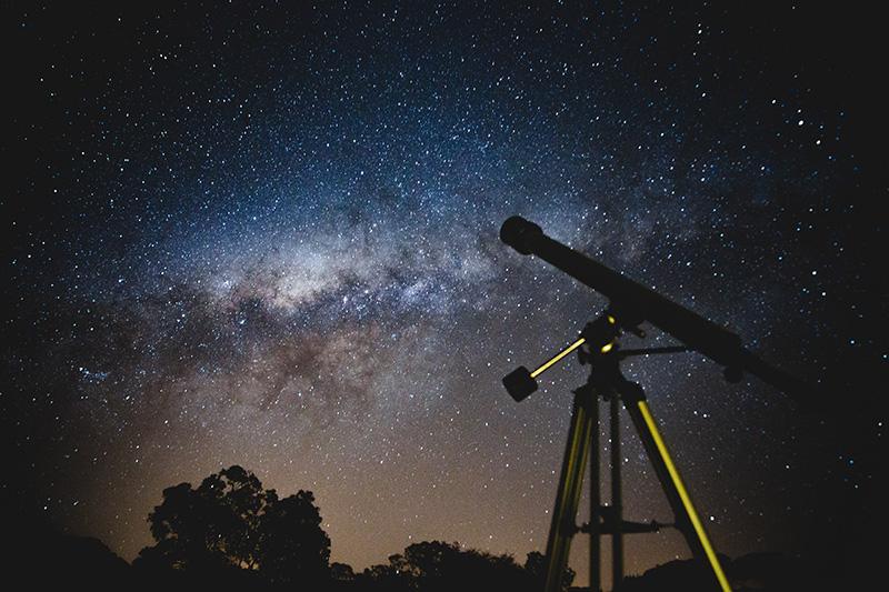 Fernrohr steht unter Sternenhimmel