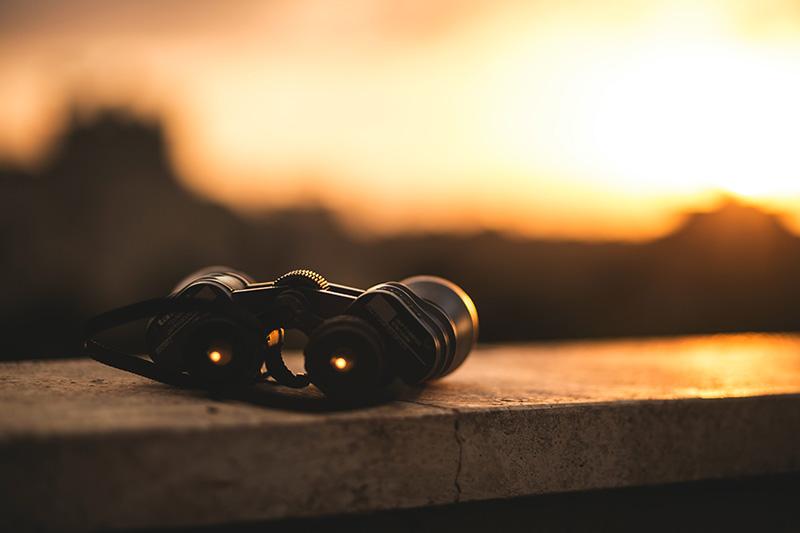 Fernrohr auf einer Steinmauer bei Sonnenuntergang