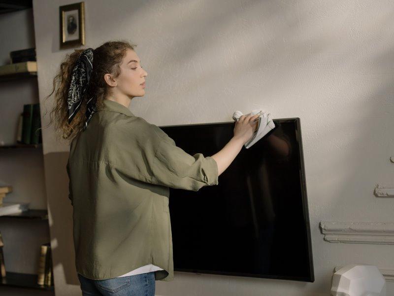 Frau die einen Fernseher reinigt