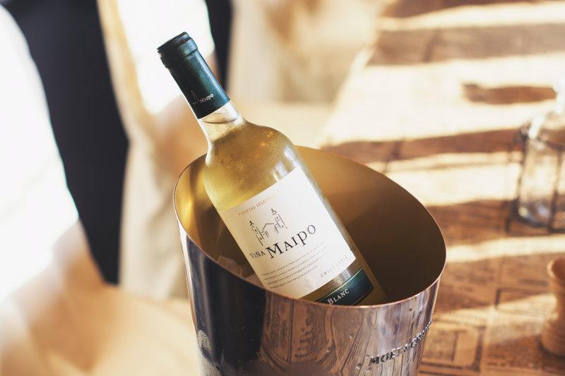 Flaschenkühler mit Weißwein und Eiswürfel