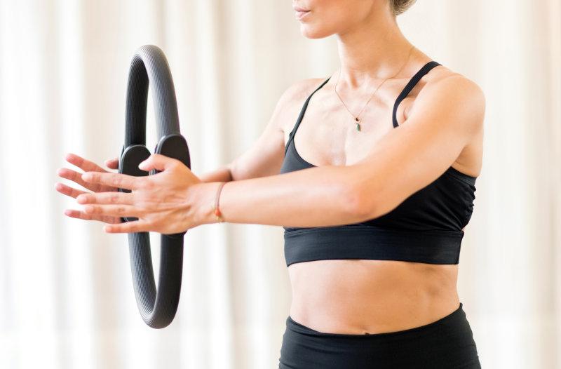 Frau benutzt Pilatesring im Workout