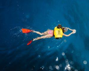 Eine Frau schwimmt mit einem Schwimmrucksack
