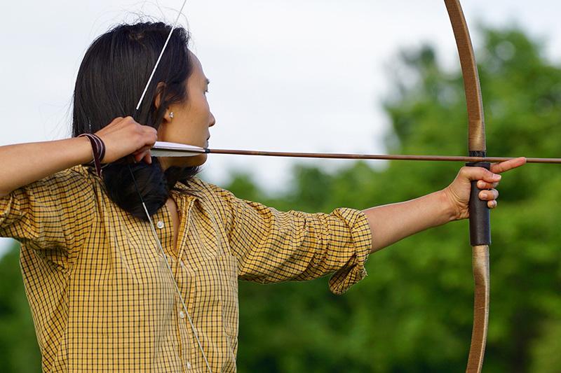 Frau zielt mit ihrem Bogen
