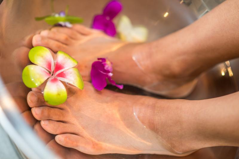 Frau nimmt Fußbad mit Blumen im Wasser