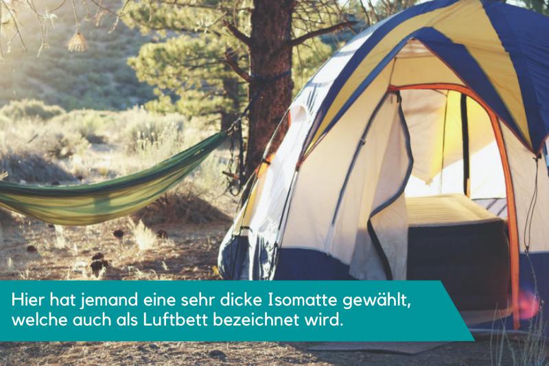 Landschaft mit einer Hängematte und einem Zelt, in dem eine Isomatte liegt