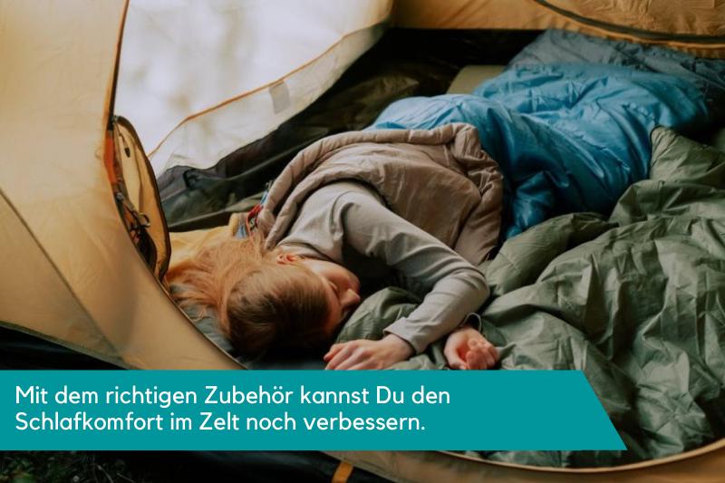 Frau liegt in einem Zelt auf einer Isomatte in einem Schlafsack