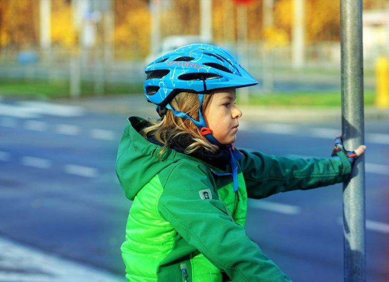 Ein Kind mit einer Fahrradjacke auf dem Fahrrad